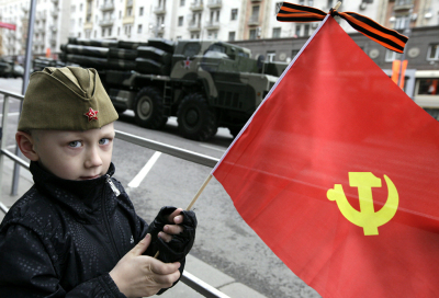 A Russian boy watches armoured vehicles